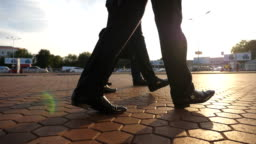 Feet of three businessmen walking in city with sun flare at background. Unrecognizable business men commute to work together. Confident guys being on his way to office. Colleagues going outdoor. Slow motion Close up Low angle view