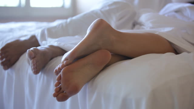 cu feet of two people in bed / stowe, vermont, united states - hotel stock-videos und b-roll-filmmaterial
