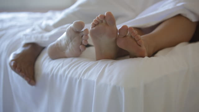 PAN Feet of two people in hotel bed / Stowe, Vermont, United States