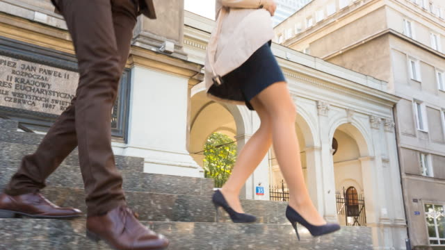 CU feet of well dressed couple hurrying down stairs