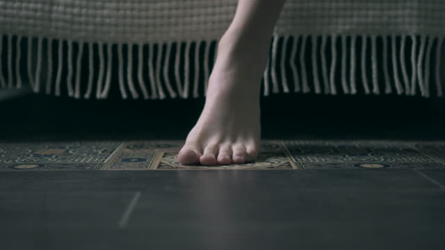 feet of woman getting out the bed in the morning - pavimento video stock e b–roll