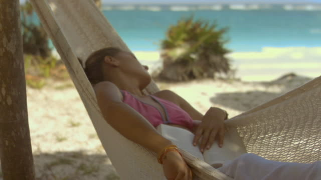 CU Feet of woman sleeping in hammock/ PAN MS Woman sleeping in hammock with beach in background/ Tulum, Mexico