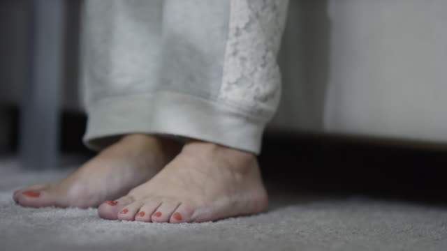 Feet of woman standing on carpet in the morning