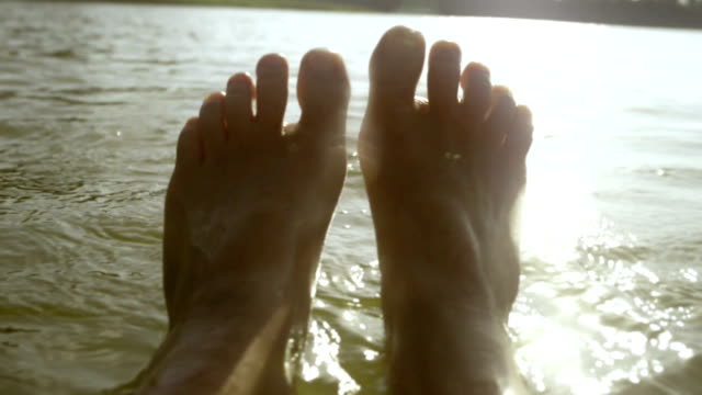 Feet of woman while drifting on water, POV