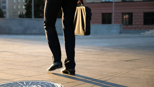 Feet of young businessman with a briefcase walking in city street. Business man commuting to work. Confident guy in suit being on his way to work. Cityscape background. Slow motion Rear view Close up