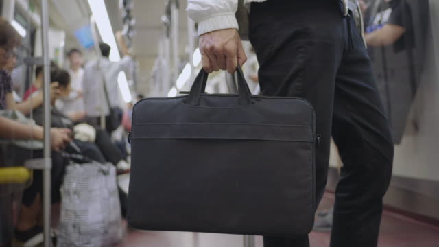 feet of young businessman with a briefcase walking in city street. business man commuting to work. confident guy in suit being on his way to work. electric train. slow motion rear view close up - human limb stock videos & royalty-free footage
