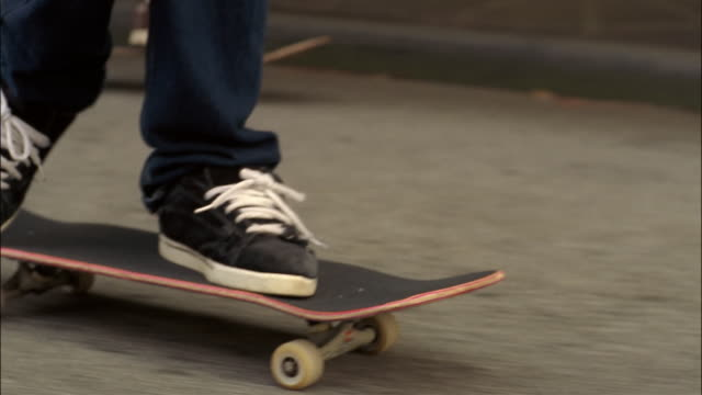 feet of young men skating down street / skater kneeling on board / performing ollie - scarpe da ginnastica video stock e b–roll