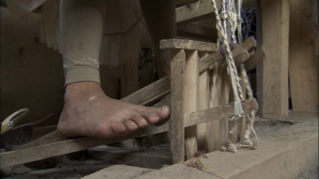 Feet on treadles to move the heddles during silk weaving, Hetian, Xinjiang province, China