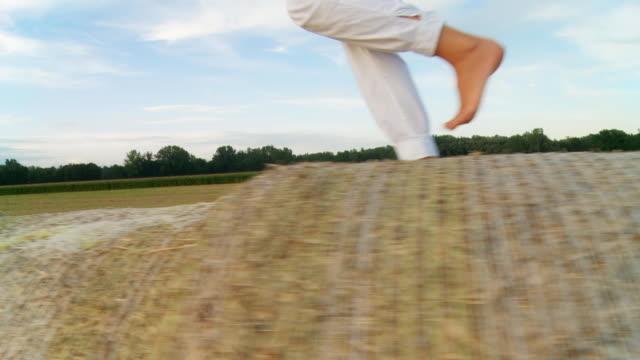 vidéos et rushes de hd prise stable: course sur foin bales carrés - joggeuse