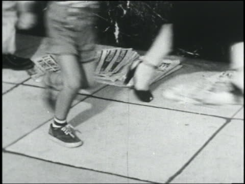 b/w 1950 feet running over pile of newspapers on sidewalk during air raid - crowd running scared stock videos & royalty-free footage