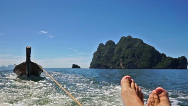 vidéos et rushes de pieds jusqu'à se détendre en regardant vue mer île sur voyage de bateau de vacances été - assis en tailleur