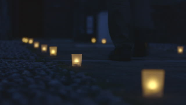 vídeos de stock e filmes b-roll de feet walk on paved pathway lined with candles - footpath