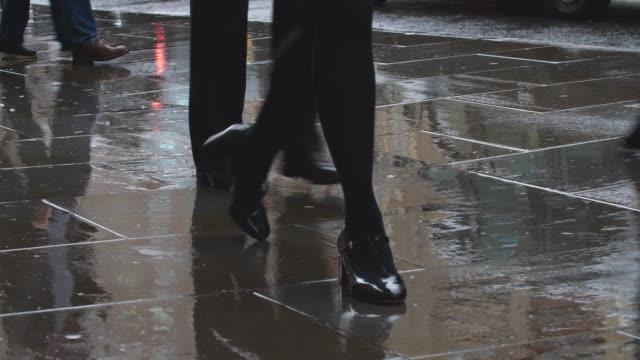 Feet walking in city rain. Smartly dressed woman, lower body.