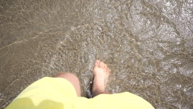 Füße, die zu Fuß in das Wasser in einem Strand auf Bali, Indonesien