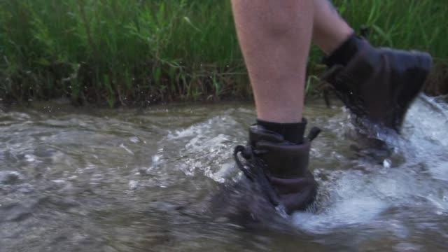 vídeos de stock e filmes b-roll de feet walking through river water - 50 54 anos