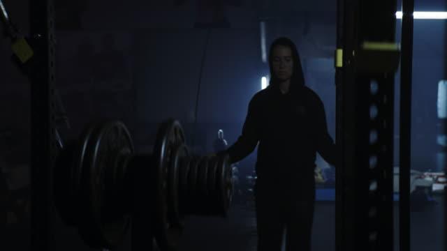 stockvideo's en b-roll-footage met mma femal vechter springtouw training. portret bij donkere gymnastiek - touw