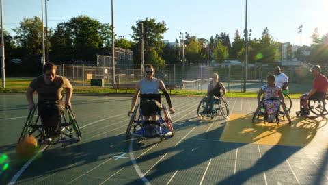 vídeos y material grabado en eventos de stock de ms female adaptive athlete dribbling ball down court during wheelchair basketball game on summer evening - comunidad