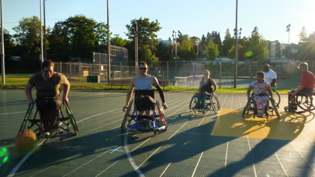 stockvideo's en b-roll-footage met ms female adaptive athlete dribbling ball down court during wheelchair basketball game on summer evening - minder validen