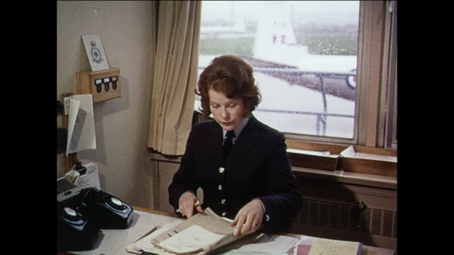 montage female adjutant working in an office alongside male royal air force members and movement officers guiding a family as they're walking across a runway towards a plane / united kingdom - royal air force video stock e b–roll