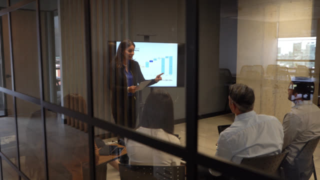 female adult manager addressing her team using a visual aid during a business meeting at the office - teamwork stock videos & royalty-free footage