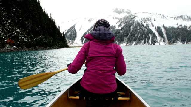 female adventurer canoeing an alpine lake - surrealism stock videos & royalty-free footage