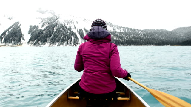 female adventurer canoeing an alpine lake - canoe stock videos & royalty-free footage