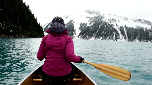 female adventurer canoeing an alpine lake - traditionally canadian stock videos & royalty-free footage