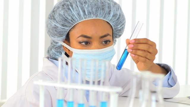 female african american scientist analyzing blue liquid in a test tube - haarnetz stock-videos und b-roll-filmmaterial