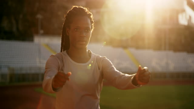 slo mo female african-american athlete stretching in the stadium at sunset - african ethnicity stock videos and b-roll footage