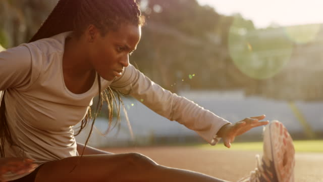 SLO MO Female African-American athlete stretching in the stadium in setting sun