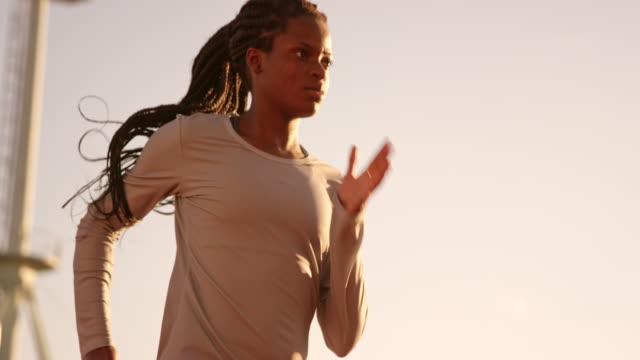SLO MO DS Female African-American athlete with long braided hair running in stadium at sunset
