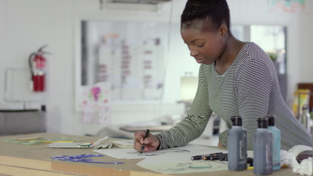 female african-american designer sketching at a drawing table - illustrator stock videos & royalty-free footage