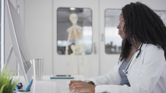 stockvideo's en b-roll-footage met vrouwelijke afro-amerikaanse arts achter een computer zit - testuitslag