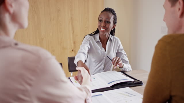 female african-american insurance agent shaking hands with clients - brochure stock videos and b-roll footage