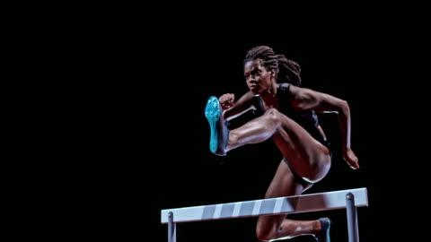 vídeos y material grabado en eventos de stock de slo mo ld female african-american sprinter jumping over a hurdle - pasatiempos