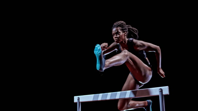 SLO MO LD Female African-American sprinter jumping over a hurdle