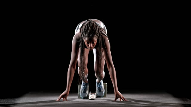 vídeos de stock, filmes e b-roll de slo mo ld female african-american sprinter taking off from the starting blocks - atleta