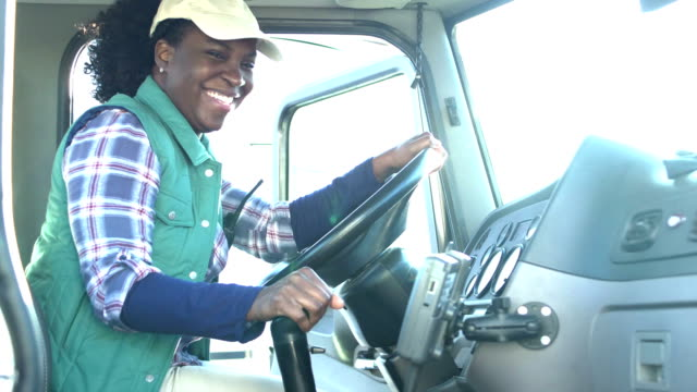 vídeos de stock, filmes e b-roll de o excitador africano-americano fêmea do caminhão senta-se no semi-caminhão - caminhão