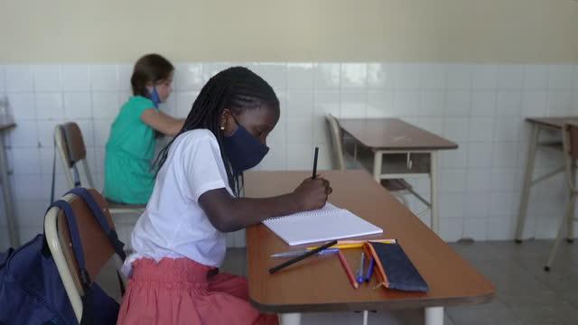 教室で授業をしている女性のアフロアメリカ人の生徒。コーヴィッド-19 コンセプト - 消しゴム点の映像素材/bロール