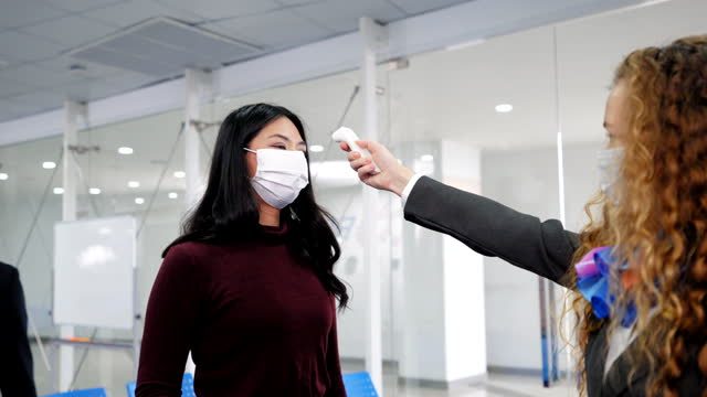 female airline check-in attendant checking body temperature of all airline passengers with a protective mask is handing over his passport at the airline counter check-in for disease prevention covid-19 at the airport for new normal travel. - examining stock videos & royalty-free footage