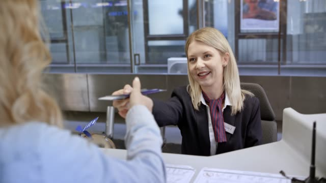 female airline employee at the check in desk handing passport to the passenger - luggage stock videos & royalty-free footage