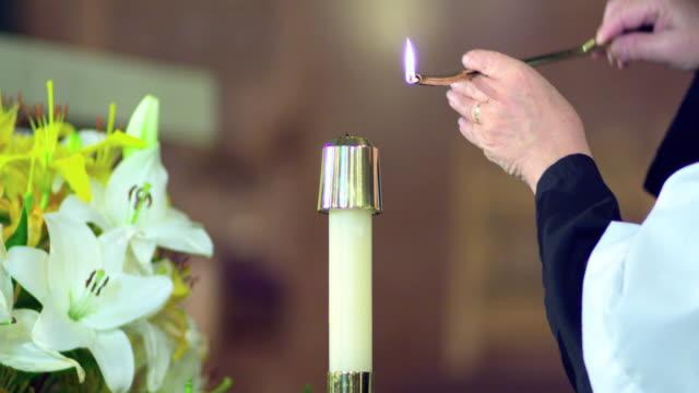 vidéos et rushes de cu female altar server's hand lighting candle at altar, manhattan beach, california, usa - candlelight