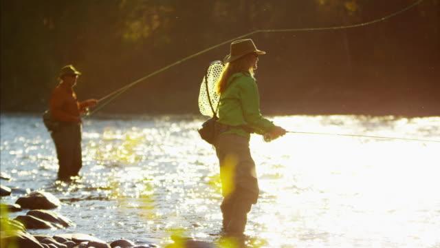 vidéos et rushes de female and male casting line freshwater fishing usa - lancer la ligne de canne à pêche
