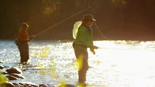 stockvideo's en b-roll-footage met female and male casting line freshwater fishing usa - hengel uitwerpen
