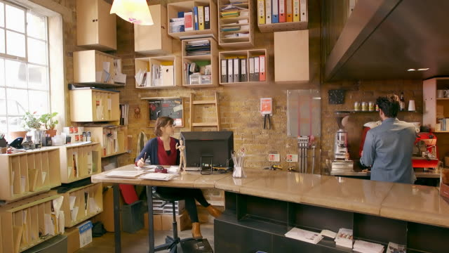 vídeos de stock e filmes b-roll de female and male employees discuss work over coffee in creative office space - small office