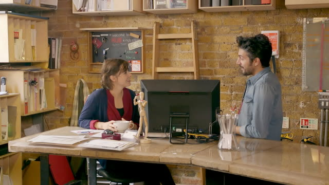 Female and male employees discuss work over coffee in creative office space