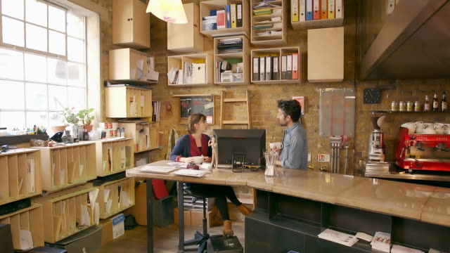 female and male employees discuss work over coffee in creative office space - modern stock videos & royalty-free footage
