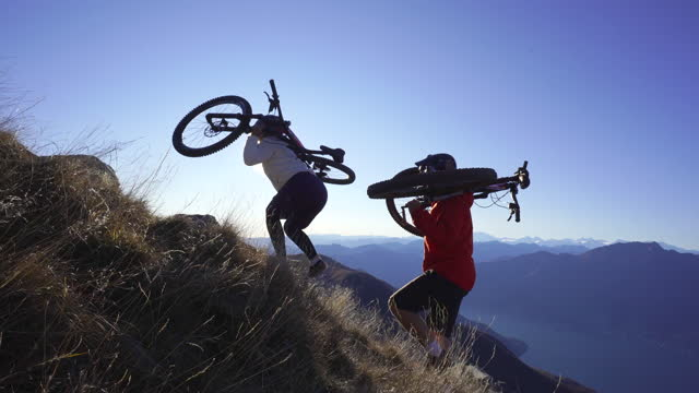 vidéos et rushes de female and male mountain bikers ascend mountainside - tenir