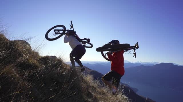 female and male mountain bikers ascend mountainside - freizeitaktivität stock-videos und b-roll-filmmaterial
