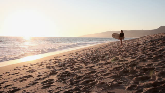 female and male surfers meeting on the beach at sunset - malibu stock videos & royalty-free footage